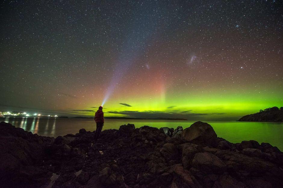 Une personne regardant une Aurore Australe rouge et verte